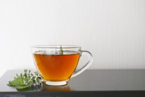 clear glass tea cup with hot herbal tea sitting on a counter