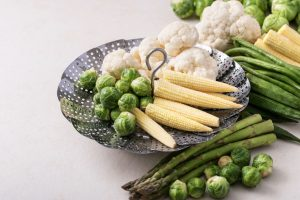 metal steamer basket with corn, brussel sprouts, and cauliflower and asparagus steamed vegetables