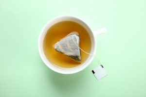Green tea bag in a white tea cup glass on counter