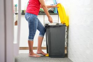 Woman throwing away trash in a garbage can in the kitchen with a touchless foot pedal